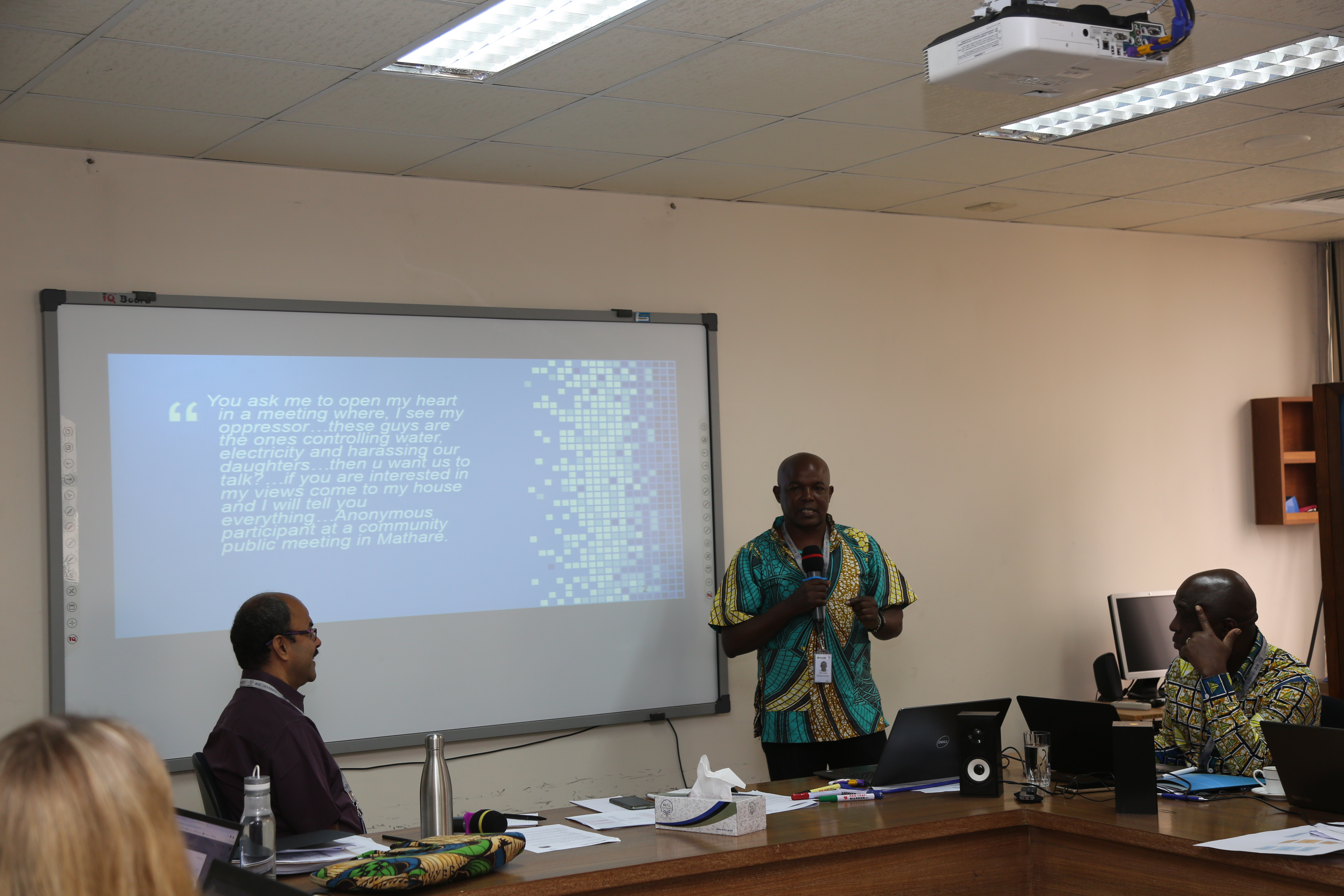 Kimani presenting in front of a slide with the quote from the blog on it