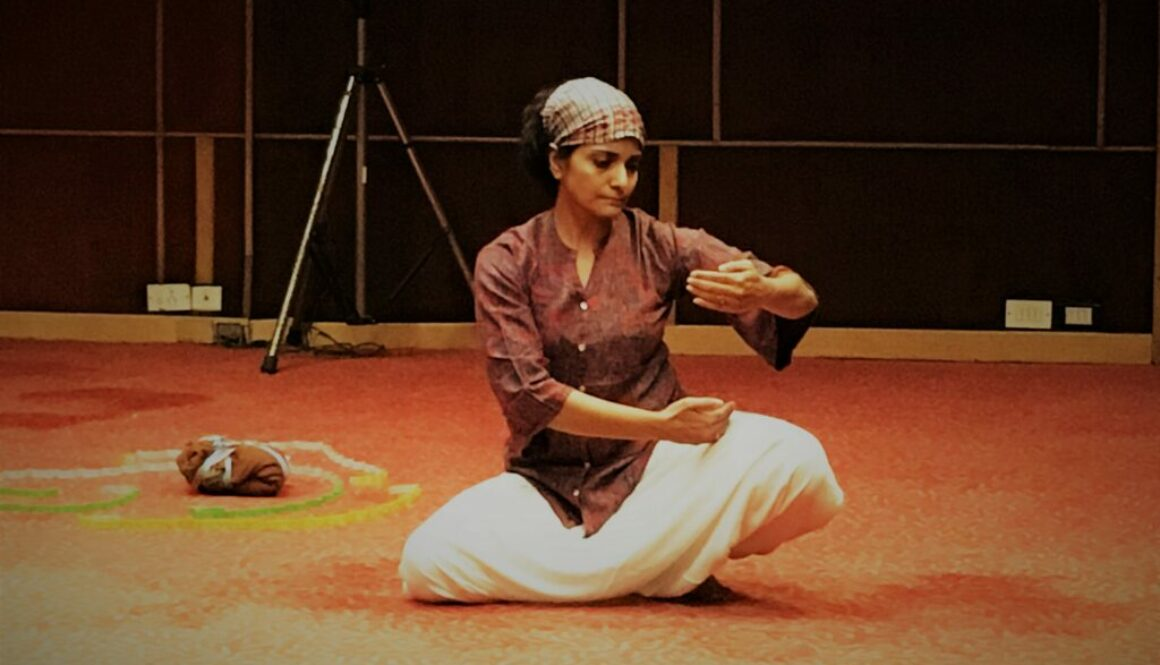 A woman sits cross legged on the floor. She is wearing white bottoms and an orange top. Her hair is tied back in a short scarf. She holds her arms out in front of her in a graceful dance move. She looks down to her fingertips. Her eyes are lowered. The carpet underneath her is an orange colour and behind her is dark wood paneling.