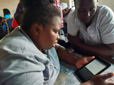 Woman on tablet during CHV mapping of Mukuru