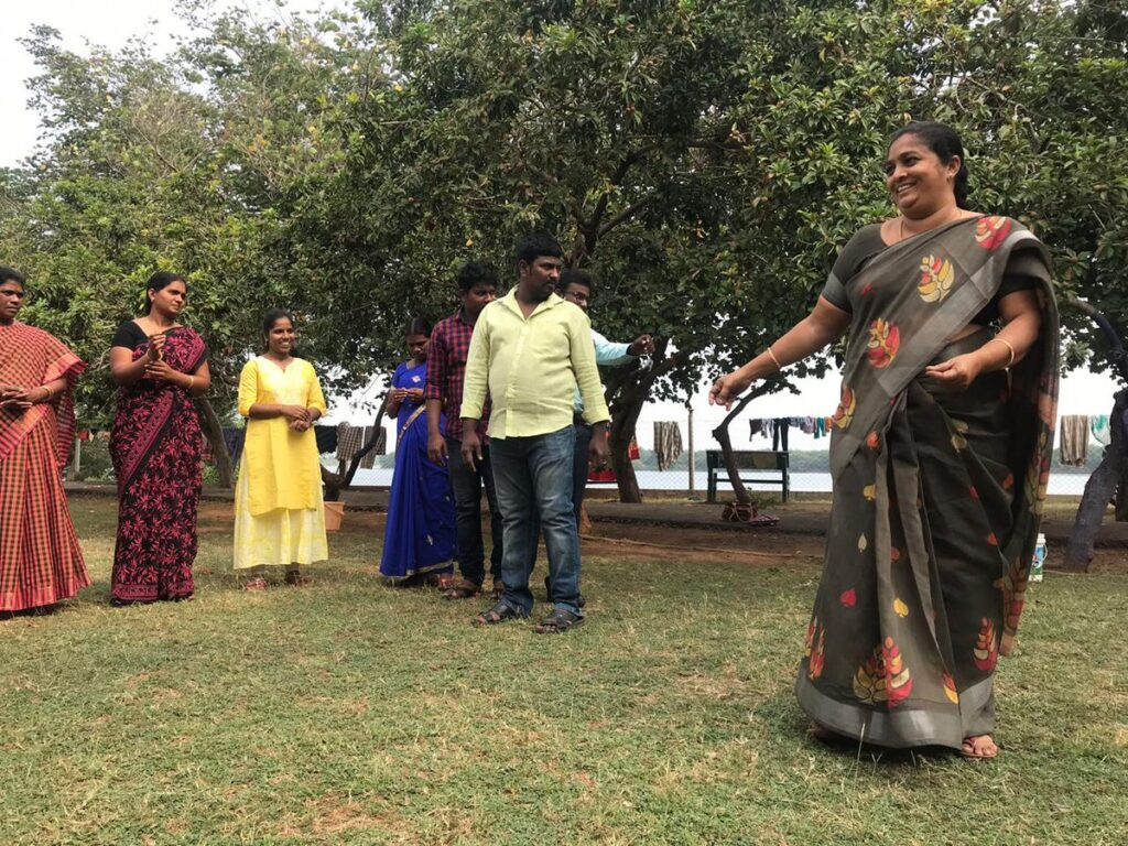 Smiling woman performing in a play. She is wearing a brown and orange patterned sari and she has long dark hair which is tied back. She has her arms outstretched almost as if she is dancing. Behind her a row of her colleagues look on. They are outside in a grassy area under some trees.