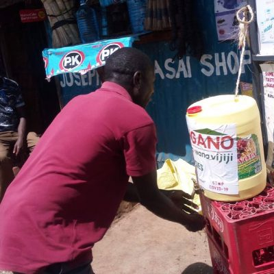 A man in a red t-shirt bends over to wash his hands to prevent the spread of COVID19 at a stand in Kibera Nairobi