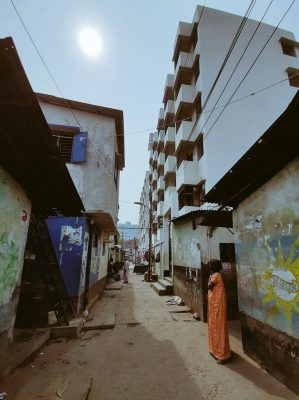 The sun is faint through the haze in Dhalpur as a women in an orange dress stands in a deserted ally and looks to the sky