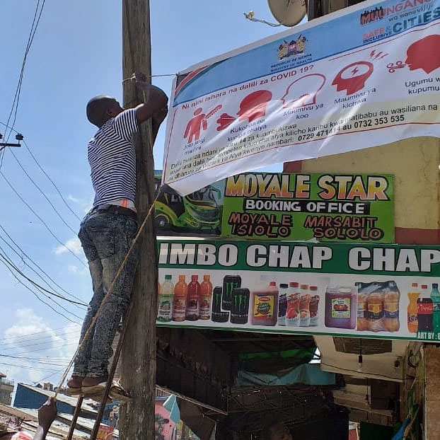 Youth from Huruma puts up a Covid-19 information banner around one of the settlements major roads by Know Your City Tv.