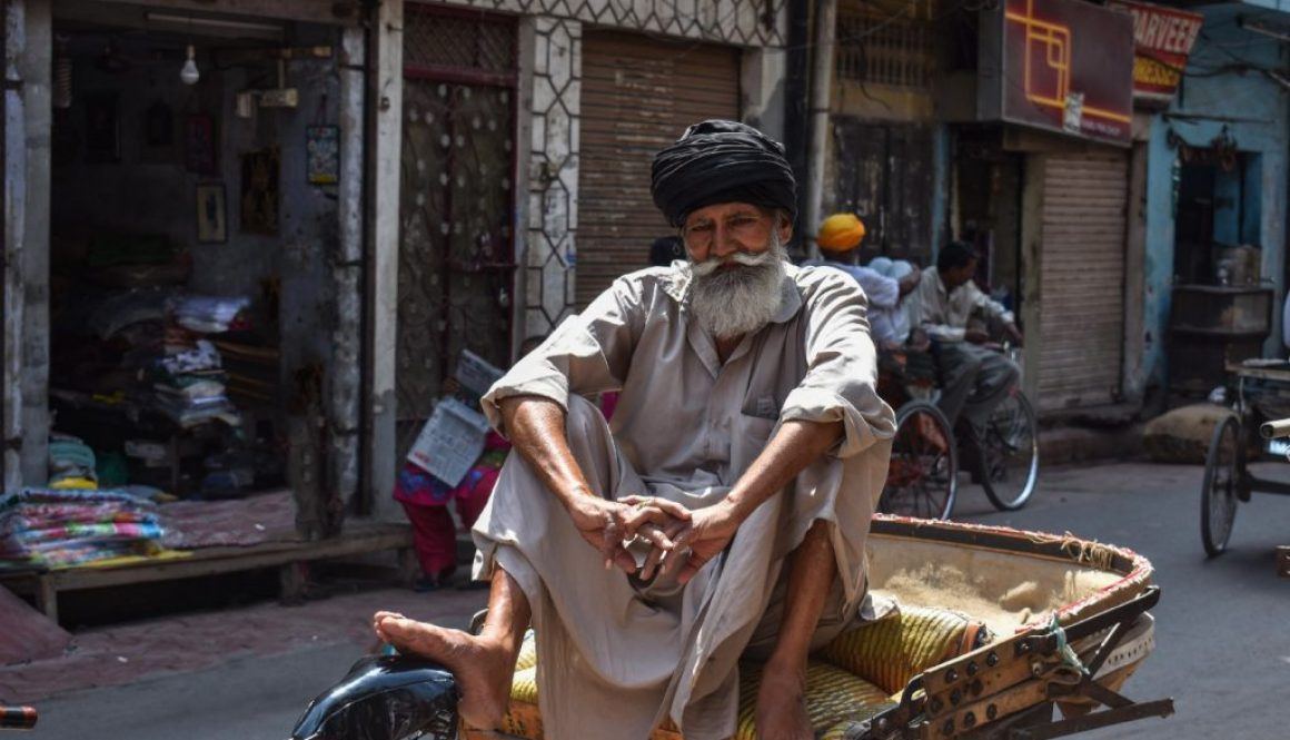 A rickshaw owner with an insecure livelihood sits cross legged facing the camera. He is older and he has a long white beard