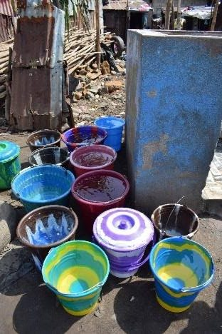 Buckets of water to be carried by resident women and girls to their homes